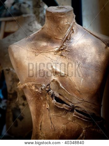 Old vintage mannequin painted in gold and slashed