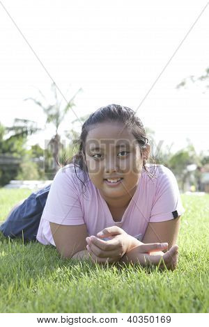 ?girl lied on green grass field with nice emotion