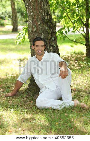 Man in white sitting under a tree