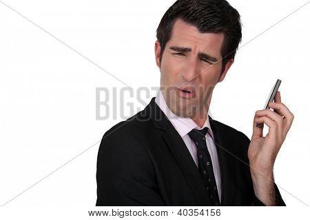 Businessman grimacing at his phone