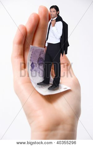 Businessman stood on giant hand carrying money