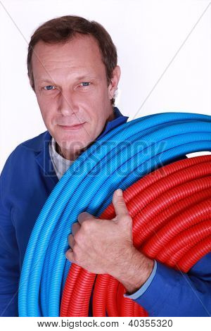Electrician with rolls of blue and red corrugated plastic tubing