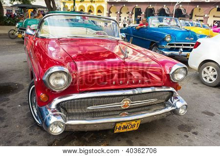 HAVANA-DECEMBER 14:Shiny red 1957 Buick waiting for tourists near a hotel December 14,2012 in Havana.Thousands of these cars are in use in Cuba and they have become an famous symbol of the country