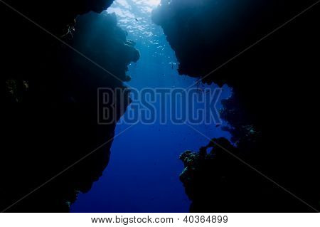 Sun Beams Filtering Down Through The Ocean's Surface Through A Small Cave Exit
