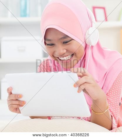 Southeast Asian teenager listen mp3 headphone at home. Muslim teen girl living lifestyle.