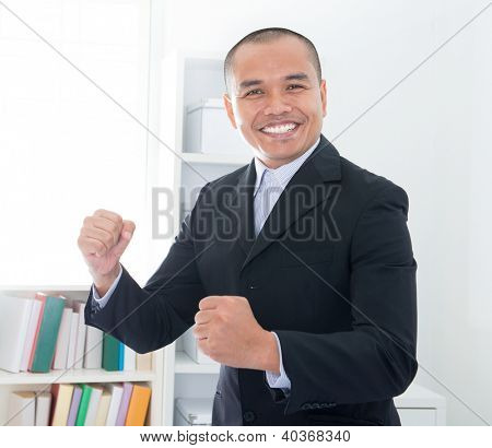 Cheerful Southeast Asian businessman smiling in office