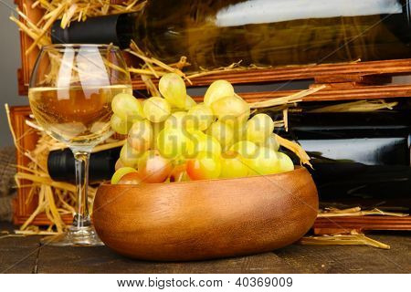 Wooden case with wine bottles, wineglass and grape close up