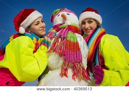 Side view of two girls with snowman outdoor on a warm winter day
