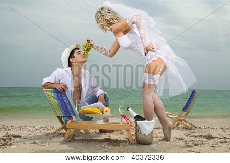 Sexy bride feeding her groom with grapes