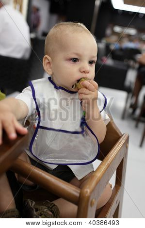 Baby Has Breakfast In A High Chair