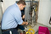 stock photo of combustion  - Plumber fixing gas furnace using electric and plumbing tools - JPG