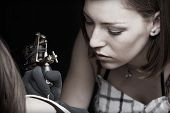 image of modification  - Girl tattoo artist works on the client - JPG