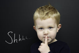 stock photo of cheeky  - Smart young boy wearing a navy blue jumper stood infront of a blackboard with his finger over his lips being quiet - JPG