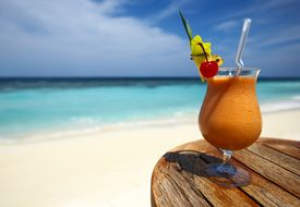 picture of beach party  - Bocal of fruity cocktail on a beach table - JPG
