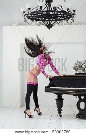 Headbanging go-go dancer in pink costume standing in room with piano