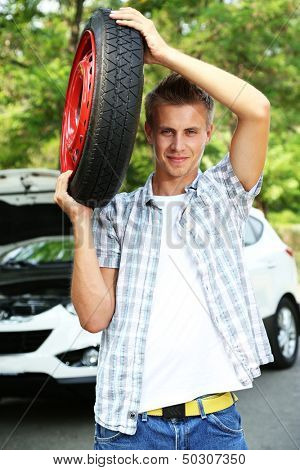 Man driver holding tire on shoulder