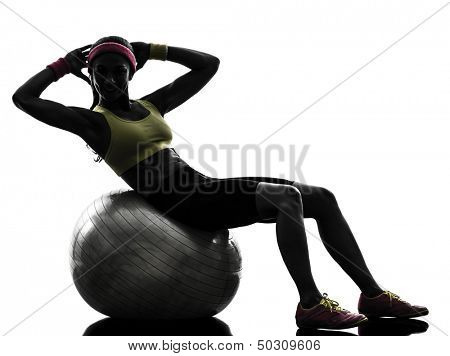 one  woman exercising crunches workout on fitness ball in silhouette  on white background