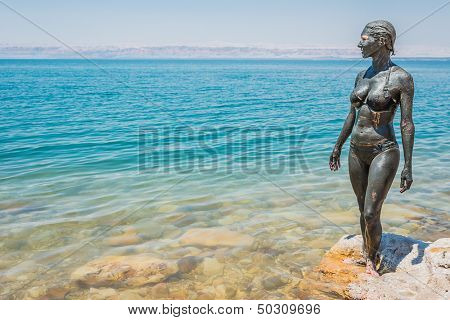 one caucasian woman applying dead sea mud body care treatment  in jordan