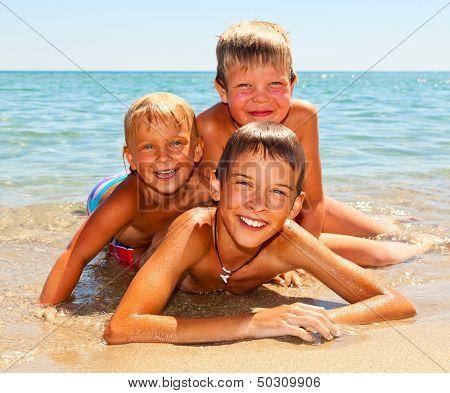 Three kids enjoying summer day on a beach