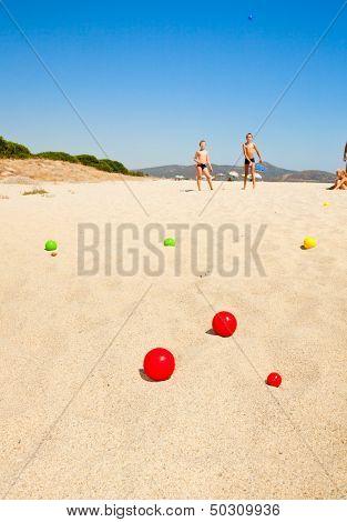 Boys playing petanque on a beach, focus on balls