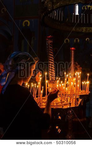 POCHAYIV, UKRAINE - AUGUST 14: Unidentified orthodox believer lights candles in Holy Dormition Pochayiv Lavra, Pochayiv, Ukraine on August 14, 2013