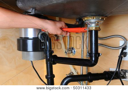 Closeup of a plumber using a wrench to tighten a fitting beneath a kitchen sink. Only the man's hand and arm are visible. Horizontal format.
