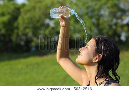 Beautiful Woman Throwing Water on  Herself  From A Bottle