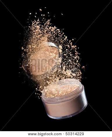 Isolated make-up powder explosion on black background