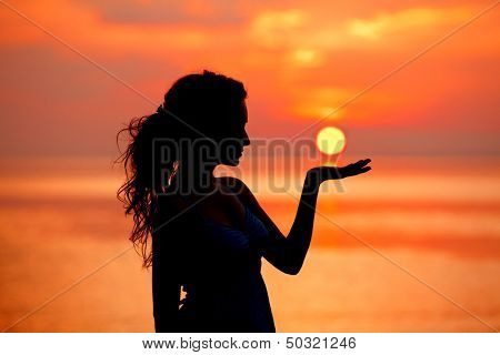 Happy free Woman enjoying in Sea Sunset. Silhouetted against the sunset, sunrise Sun on the palm