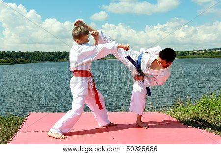 Athletes children perform paired exercises karate