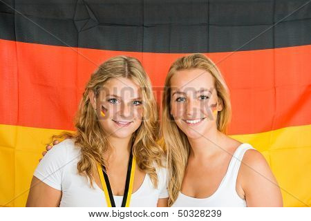 Portrait of beautiful young sportswomen standing against German flag