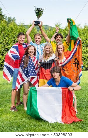 Group of international sports fans, each dressed in the color of their country and carrying the their nation's flag winning the cup together. Sportivity, friendship and globalization theme