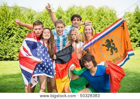 Group of international sports fans, each dressed in the color of their country and carrying the their nation's flag. Sportivity, friendship and globalization theme