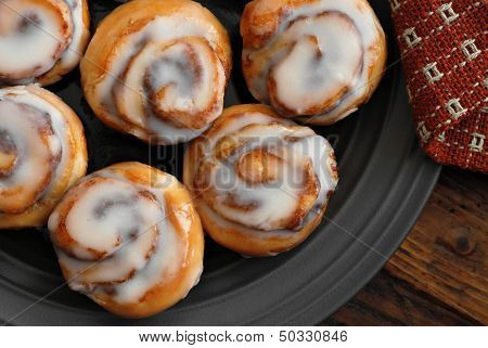 Freshly baked mini cinnamon rolls on plate with handwoven napkin and wood background.