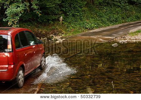 Family Car Crossing A River At Ford