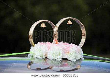 Just married gold rings and rose flowers decoration on wedding limousine car