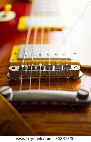 Red sunburst color single cutaway electric solid body guitar. Focus on bridge. Shallow depth of field.