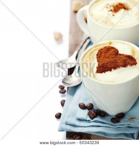 two cups cappuccino over white