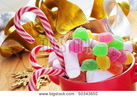 a bowl with different candies, such as candy canes, on a table with some christmas ornaments, such as a golden an silver garland and a golden star
