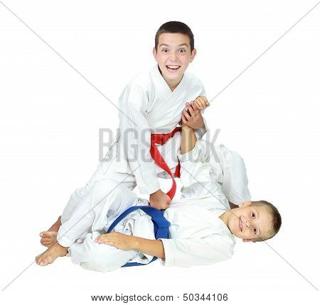 Two cheerful athlete after throwing boy beat arm another isolated