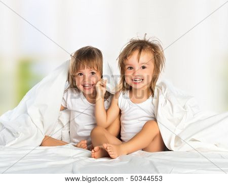 Happy Little Girl's Twin Sister In Bed Under The Blanket Having Fun