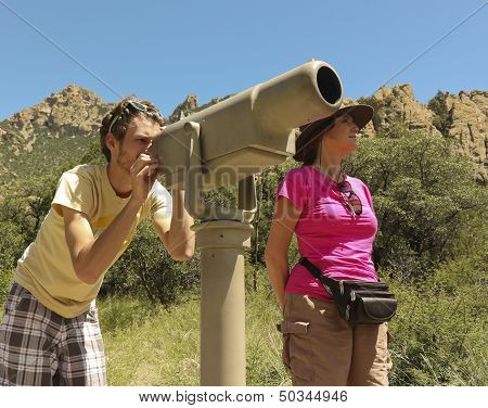 A Pair Of Hikers Use A Telescope