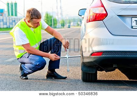 mechanic in a vest tie the wheel to the car on the road