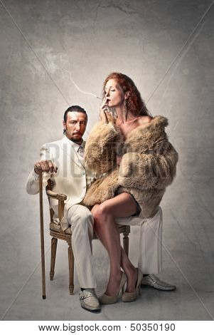 rich gangster in white dress sitting on an armchair and beautiful woman with fur smokes cigarette