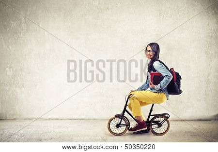 girl on bicycle with rucksack and books