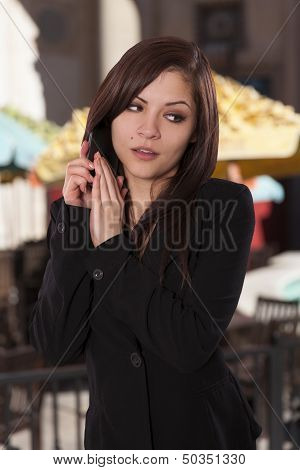 Young Woman Covers Part Of Her Phone With Her Hand.