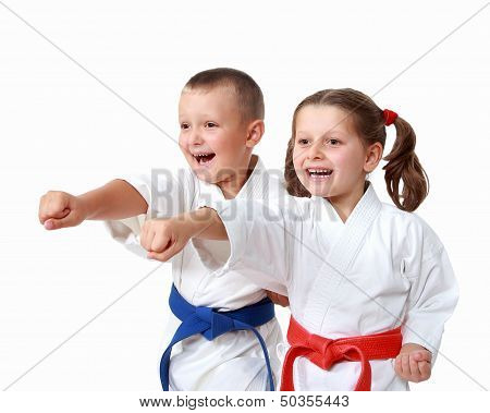 Happy athletes in a kimono beat punch arm