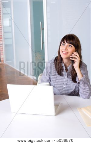 Business Woman On A Cell Phone And Laptop In Modern Office