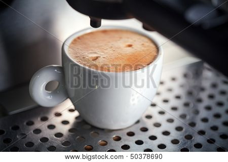 White Ceramic Cup Of Fresh Espresso With Foam In The Coffee Machine.