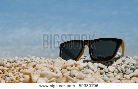 Sunglasses on the beach with small stones